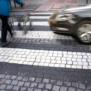 Senior citizen crossing street with fast car approaching