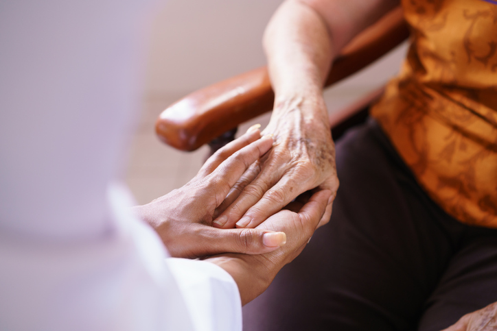 senior woman in nursing home clasped hand