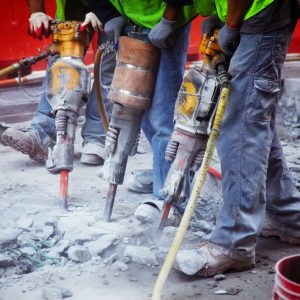 Construction workers operating jackhammers