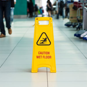 Yellow sign that alerts for wet floor in airport.Yellow sign that alerts for wet floor in airport.