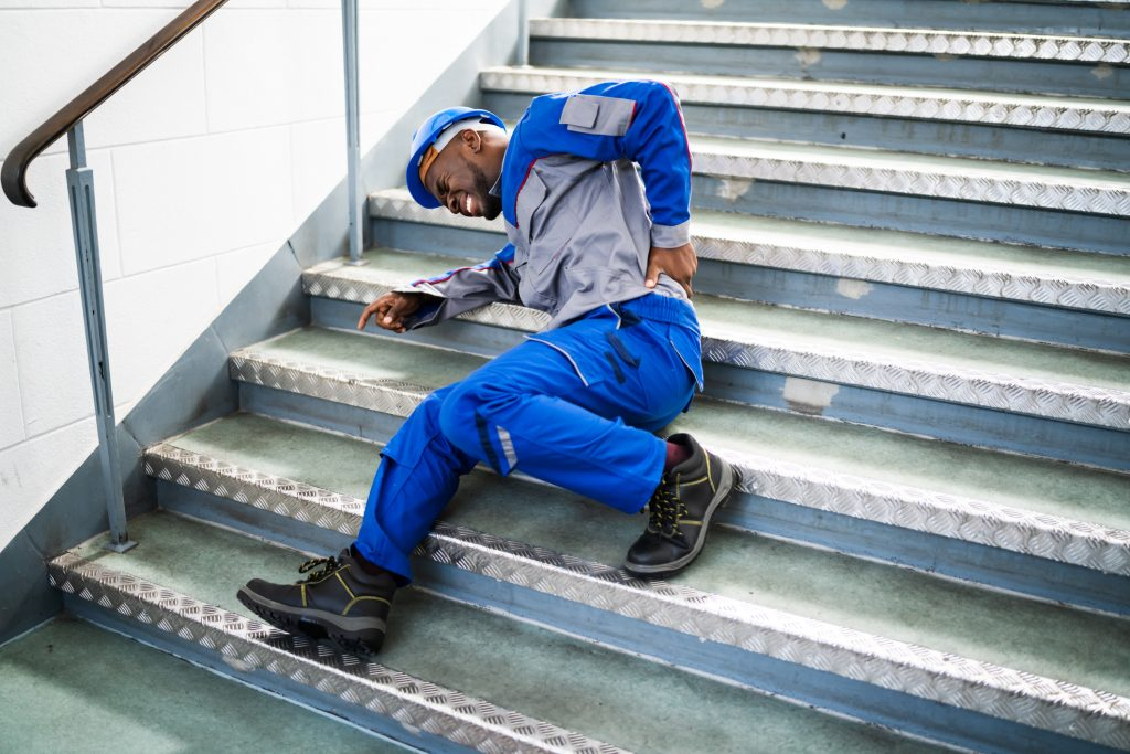 Male Worker Lying On Staircase After Slip And Fall Accident