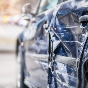 Damaged side of a blue car after an accident