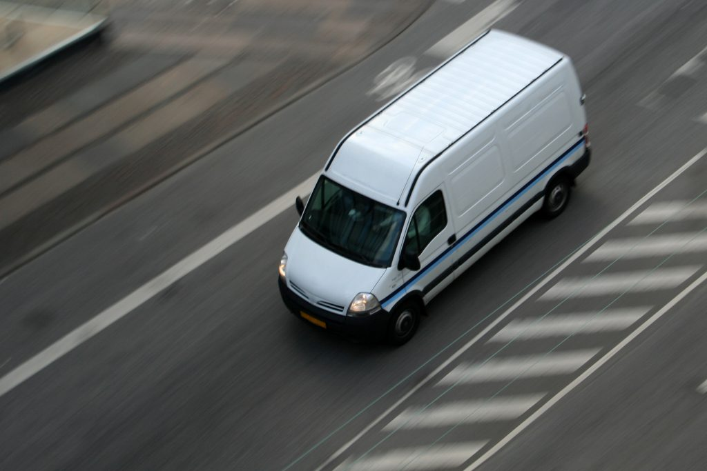 a white delivery van on the road